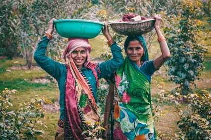 two women wearing traditional dress carrying basins