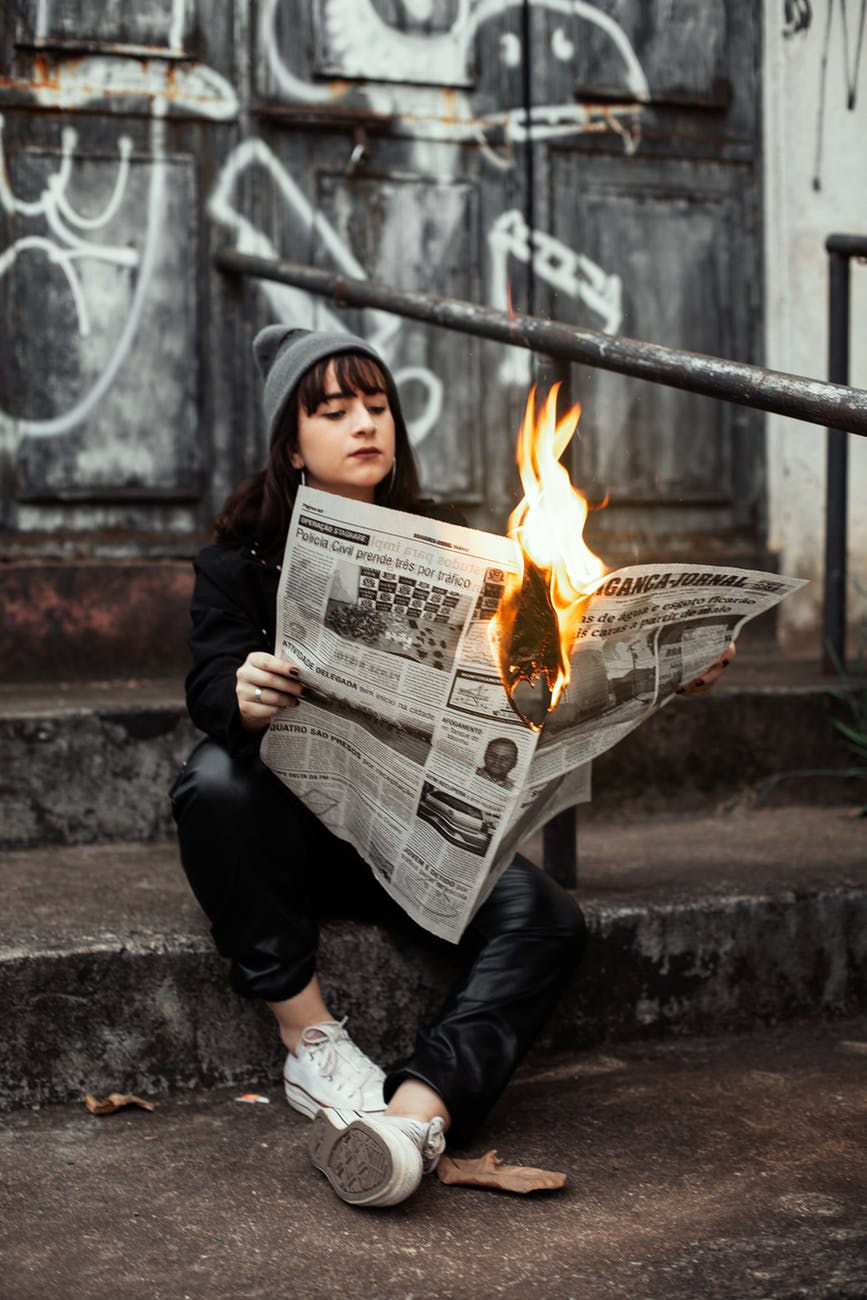 woman holding newspaper while burning