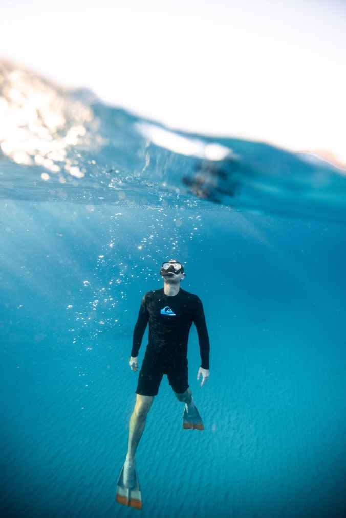 photographie à deux niveaux de l'homme sous l'eau