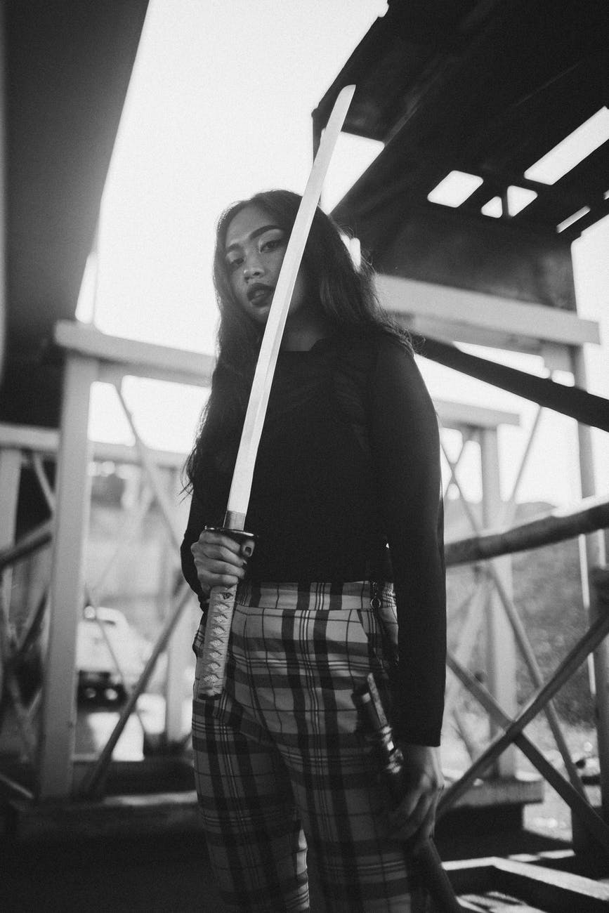 grayscale photo of woman holding katana